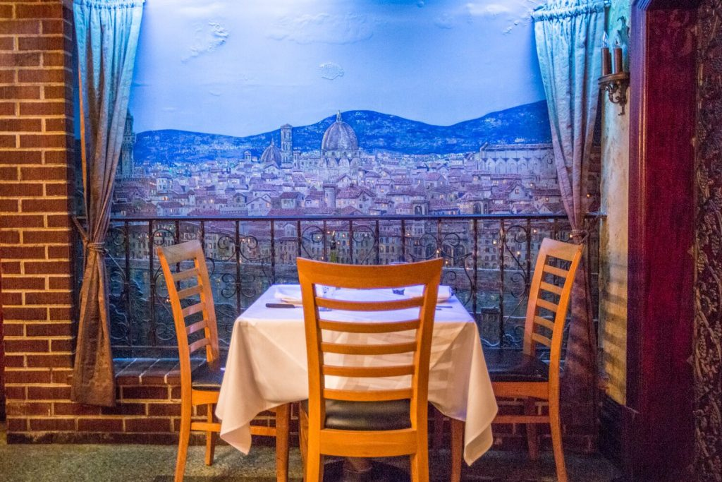 Table with three chairs facing wall with painting of Florence skyline