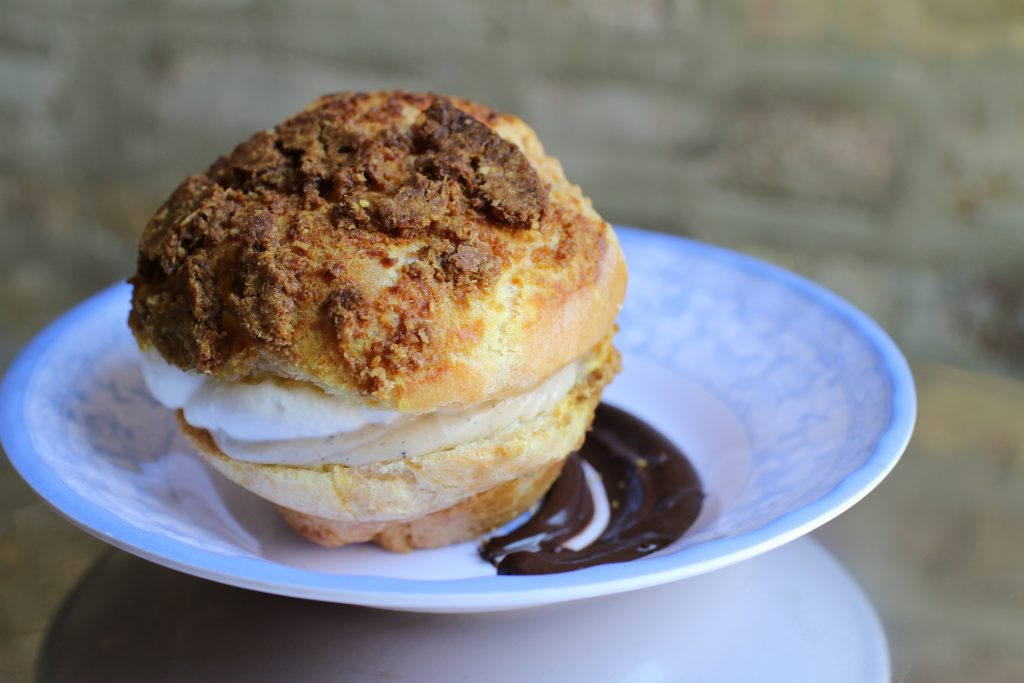 Photo of a cream puff on a white plate with a swirl of chocolate sauce.