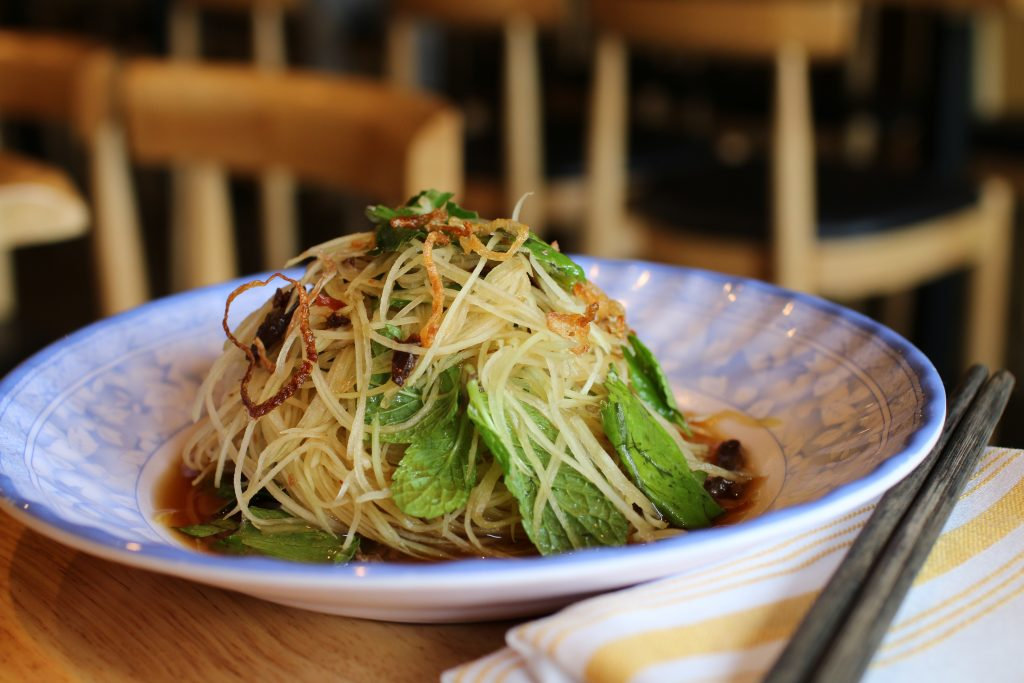 Photo of a papaya salad with basil leafs and sauce in a white and blue plate alongside chopsticks.