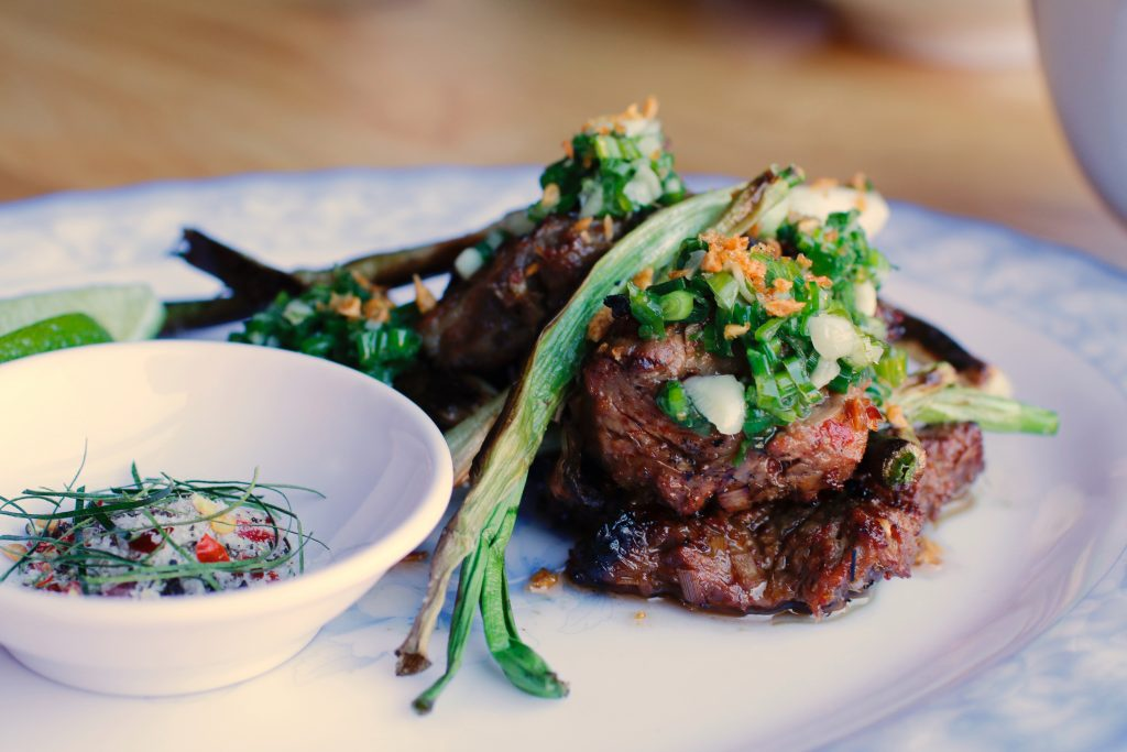 Photo of grilled ribeye with grilled scallions and a salt and herb mixture.