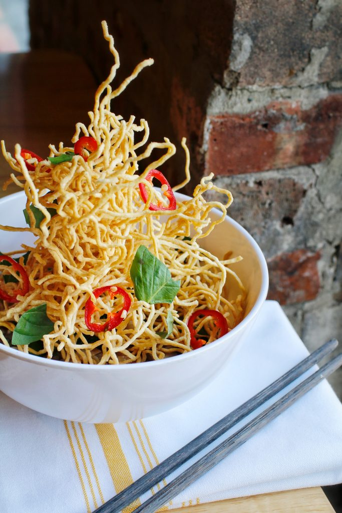 Crispy egg noodles bundled together in a plate with thinly sliced chilies and basil leafs.