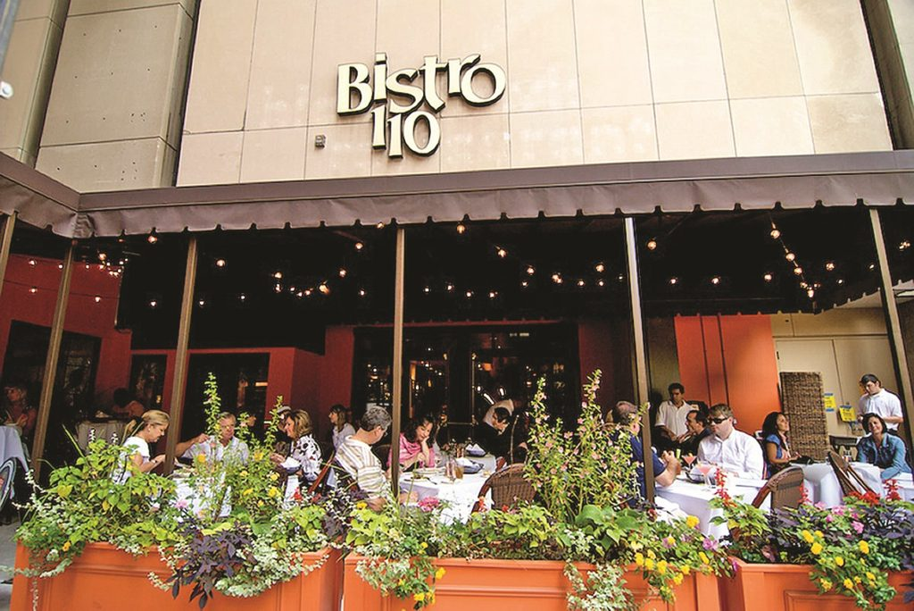 Bistro 110 patio, with diners sitting at outdoor tables near planters