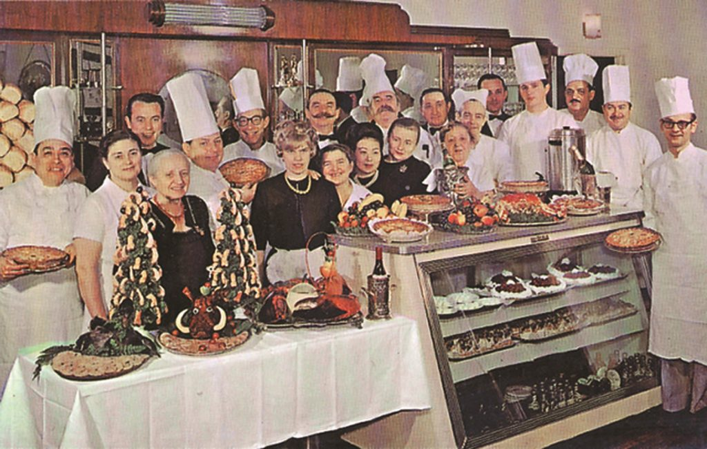 The Bakery staff standing in chef's clothing, with food displayed in front of them.