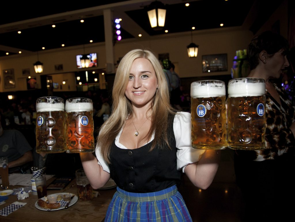 Waitress in traditional German clothing carrying four pints of beer