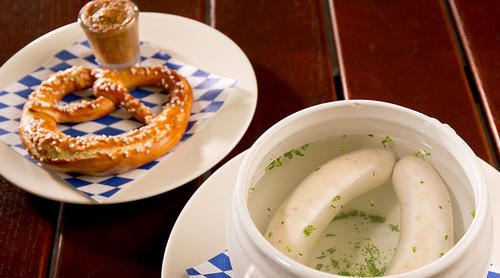 Pretzel with mustard on one plate, with weisswurst floating in water in a bowl next to it.