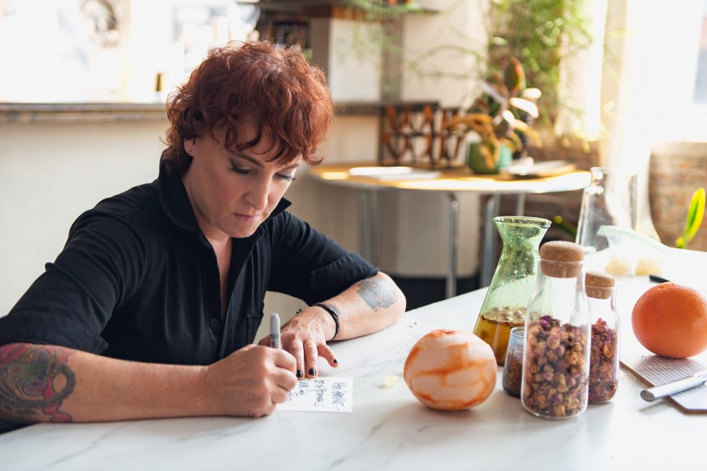 Mindy Segal writing a note with Sharpie next to oranges and other ingredients.