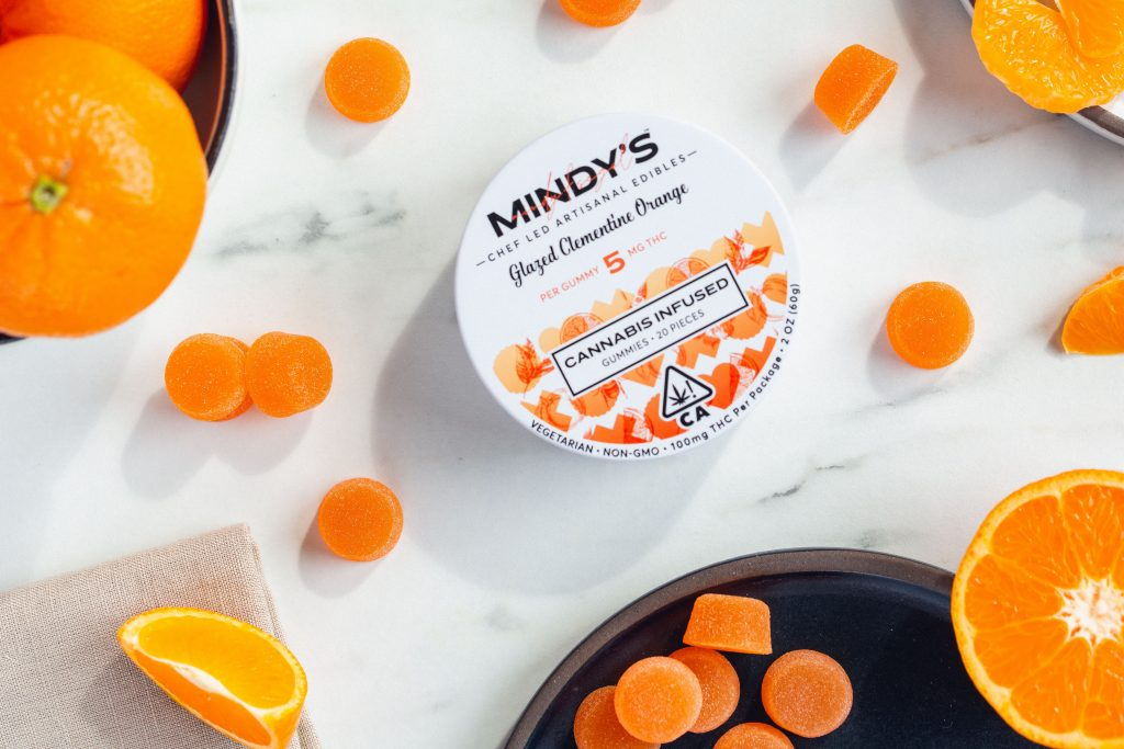 A tin of Mindy's Gummies, surrounded by sliced clementine oranges and individual gummies.